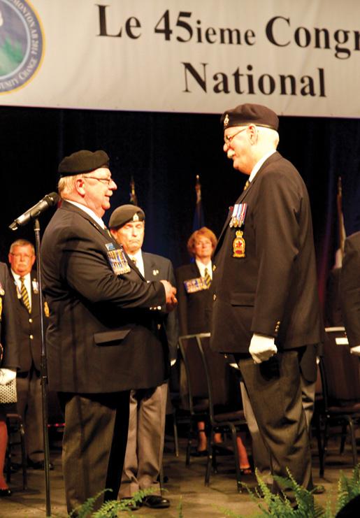 Outgoing President Gordon Moore presents the president's pin to newly installed President Tom Eagles. [PHOTO: LEGION MAGAZINE]