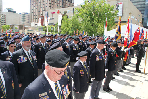 Heads bow in silence during the wreath-placing ceremony. [PHOTO: LEGION MAGAZINE]