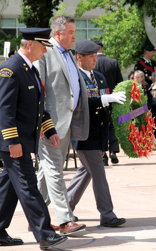 Dominion Chairman Tom Irvine assists Edmonton city councillor Dave Loken (centre) and Edmonton Fire Chief Ken Block during wreath-placing ceremonies. [PHOTO: LEGION MAGAZINE]
