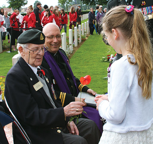 Roy Eddy receives a poppy from a young girl at Bretteville-sur-Laize Canadian War Cemetery. [PHOTO: SHARON ADAMS]