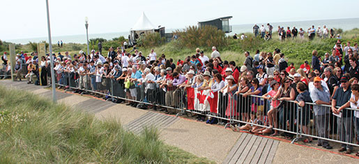 An overflow crowd of French residents and Canadian tourists line a fence outside Juno Beach Centre awaiting the official Canadian D-Day ceremony. [PHOTO: SHARON ADAMS]