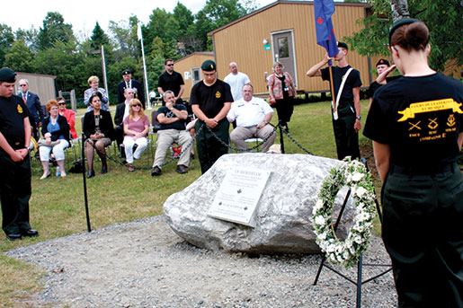 Wreaths are placed near a memorial rock where a plaque names the cadets who died in the 1974 explosion. [Sharon Adams]