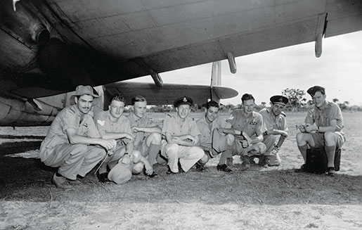 Canadian aircrew of No. 194 Squadron escape the hot sun by finding shade beneath the wing of an aircraft, April 1943. [PHOTO: LIBRARY AND ARCHIVES CANADA—PL-18001]