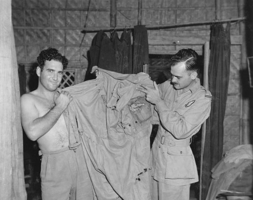 Squadron Leader James Bell (left) and Flying Officer Malcolm Forester display a flying suit that was ripped and torn by Japanese shell splinters. [PHOTO: LIBRARY AND ARCHIVES CANADA—PL-27691]