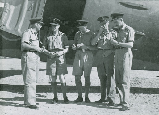 RCAF officers assemble at an airfield in Cairo, Egypt, while en route to Asia in 1944. From left are Wing Commander Paul Mathews, Wing Cmdr. H.B. Norris, Squadron Leader W.B. Woods, Wing Cmdr. Lionel Kent, and Sqdn. Ldr. W.W. McKay. [Canadian War Museum/19650071-019_14975]