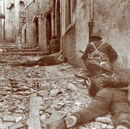 Members of the Carleton and York Regiment advance up a side street to rescue a comrade felled by a sniper's bullet in Campochiaro, Italy,  on Oct. 23, 1943. [CANADIAN WAR MUSEUM/19920085-1030]