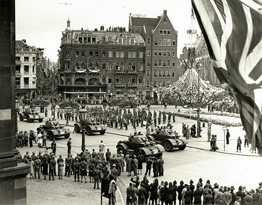 Celebrating the return of Queen Wilhelmina, Canadian troops and Dutch groups parade past the Royal Palace and Dam Square in Amsterdam on  June 28, 1945. [B.J. Gloster/DND/LAC/PA-166390]