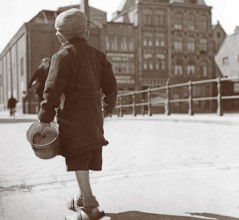Empty bucket in hand, a hopeful Dutch boy crosses a bridge in Holland during the Hongerwinter (hunger winter) of 1944-45. [LAC/e002283041]