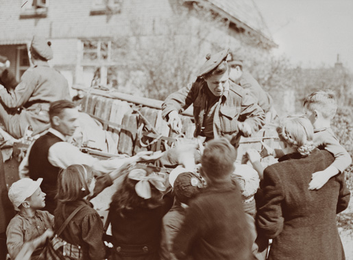 A soldier with the Stormont, Dundas and Glengarry Highlanders distributes candy to citizens in the eastern Netherlands town of Bathmen on April 9, 1945. [LAC/PA-137908]