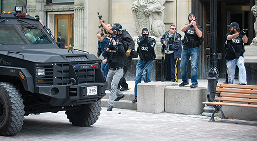 Chief of Defence Staff  General Tom Lawson  is hustled away from Parliament Hill on  Oct. 22, 2014, as security forces scan nearby rooftops for shooters. [Ashley Fraser/Ottawa Citizen. Reprinted by permission.]