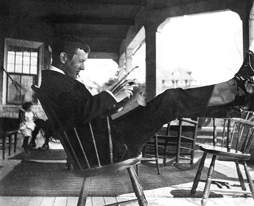 Book and cigar in hand, John McCrae relaxes at the holiday home of friends at Kennebunkport, Maine, where he spent a vacation in September 1903. [Guelph Civic Museum/M1968X.436.3]