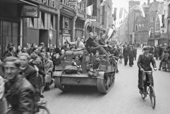 Dutch civilians in Zwolle ride on a Universal Carrier of the Régiment de la Chaudière. [LAC/PA-136176]