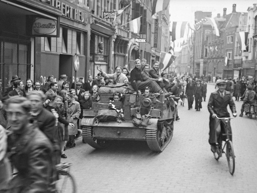 Dutch civilians in Zwolle ride on a Universal Carrier of the Régiment de la Chaudière. [LAC/PA-136176]