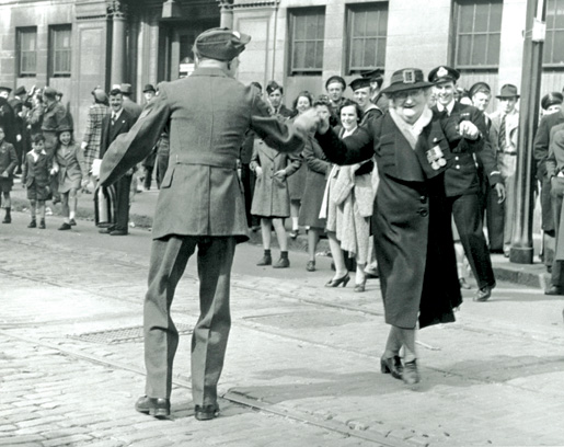 A woman dances with a soldier on Barrington Street in Halifax. Celebrations here degenerated into a riot involving thousands of servicemen, merchant seamen and civilians, forestalling official city celebrations. [LAC/C-079569]