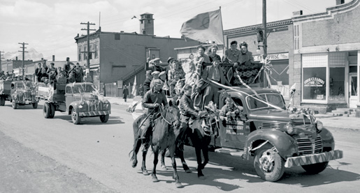Decorated pickup trucks with horseback escorts join a victory parade in Blairmore, Alta. [Glenbow Museum/nc-54-2123]