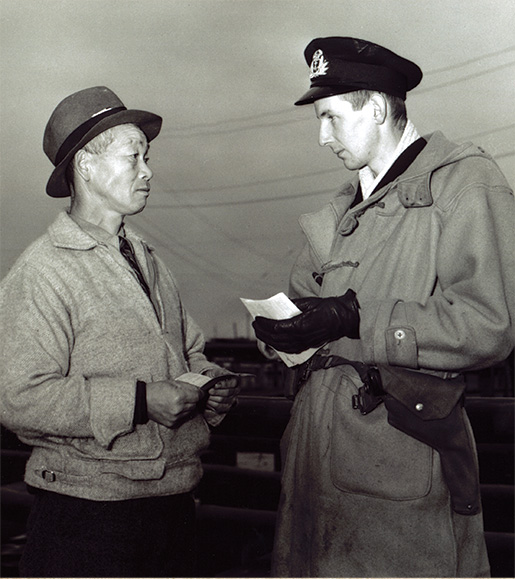 An officer with the Royal Canadian Naval Volunteer Reserve examines the papers of a Japanese-Canadian fisherman in Steveston, B.C., in December 1941. [DND/LAC/PA-170503]