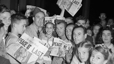 "Torontonians gather to read the Aug. 14, 1945, edition of  The Globe and Mail which ran the banner headline ""PEACE AT LAST"". [City of Toronto Archives/f1266_it98390]"