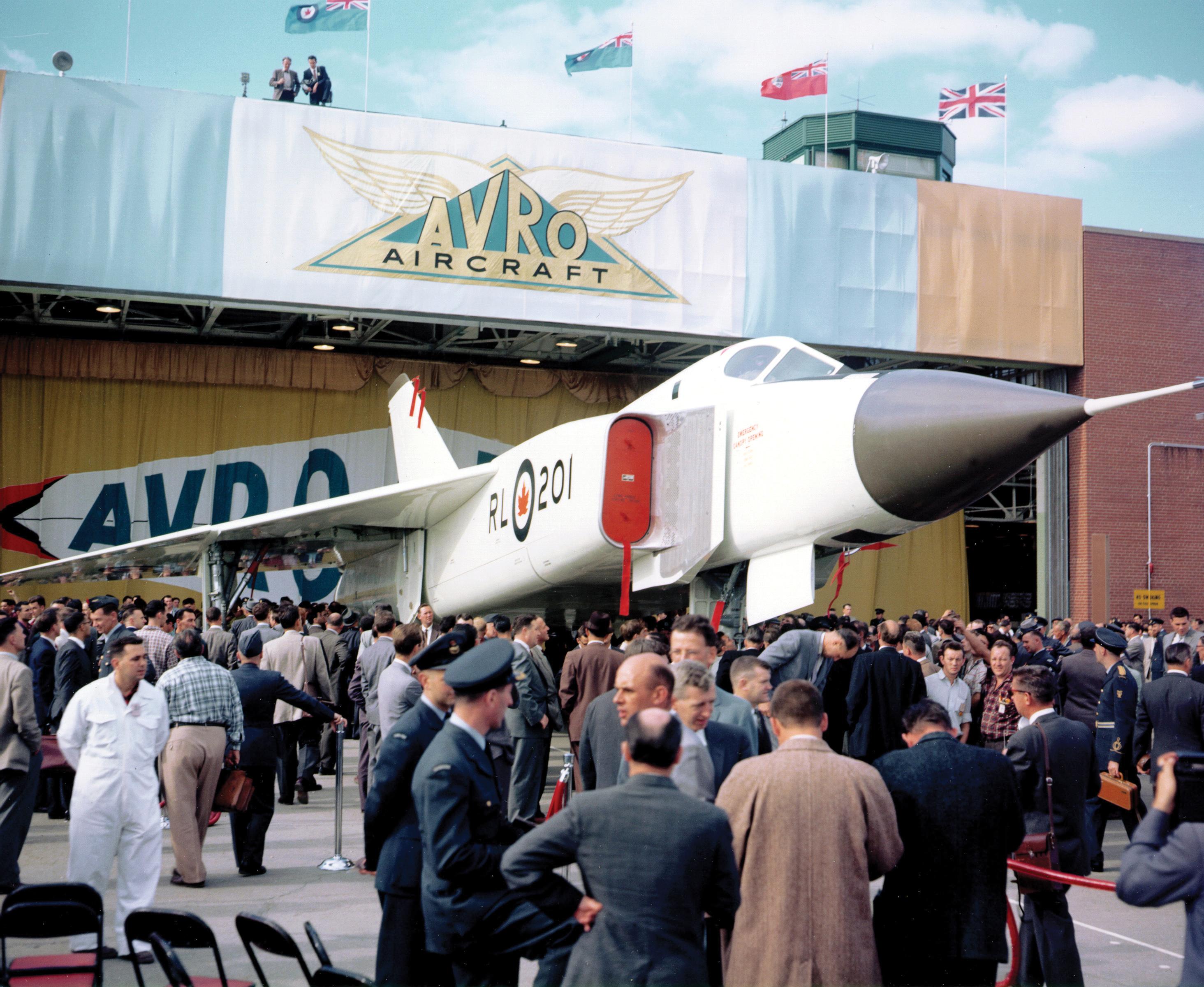 """Scan from print PCN 219 Malton, Ontario 4 October 1957 3/4 front right side view of a CF105 Jet Fighter Aircraft """"Avro Arrow"""" in Malton Ontario at the Avro Arrow Indusries Hangar. Digitalisation d'une épreuve PCN 219 Malton, Ontario 4 Octobre 1957 Vue de 3/4 de l'avant droit d'un avion de combat des Forces Canadienne (FC) de type """"CF105 Avro Arrow"""" au hangar d'aviation des industries de construction ''Avro Arrow'' à Malton, Ontario."""