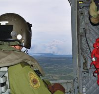 ENGLISH/ANGLAIS WA2016-0019-02  Corporal Greg Watts, Flight Engineer, observes wildfires near Fort McMurray from a CH-147F Chinook helicopter during the Canadian Armed Forces' support to the Province of Alberta's emergency response efforts.   Photo by: MCpl Brandon O'Connell, 3 CDN DIV PA Copyright Notice © 2016 DND-MDN Canada