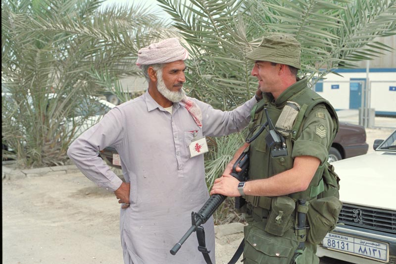 Sergeant Dan Potvin chats with a civilian while on sentry duty at the Canadian military headquarters in Bahrain. January 13, 1991.