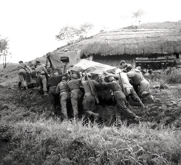 Soldiers push a jeep and trailer up a muddy slope