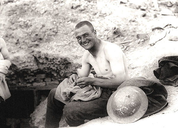 A soldier picks lice from the seams of his shirt in 1918.