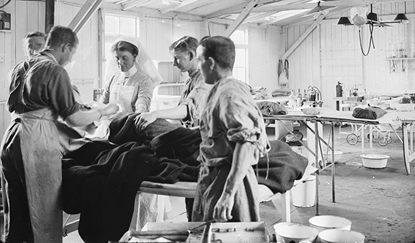 A surgeon, assistants and a nurse operate on a patient