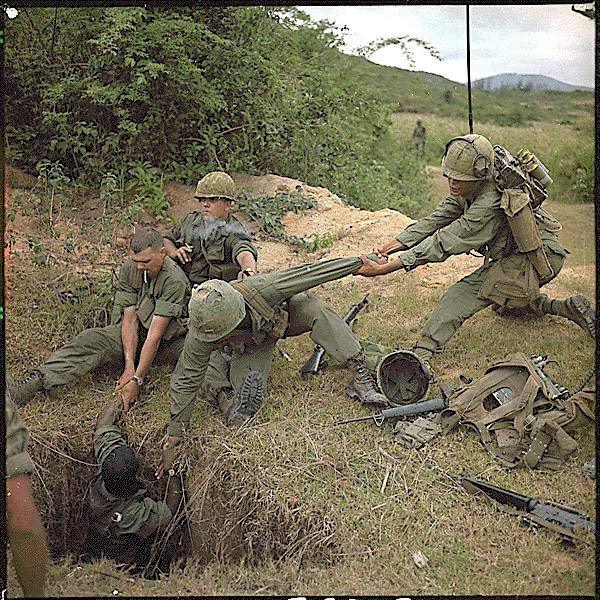American reconnaissance troops lower a tunnel rat into his office during Operation Oregon, a 1966 U.S. Marine operation northwest of Hue, Thừa Thiên Province, South Vietnam. North Vietnamese fighters would often booby-trap the tunnels with venomous snakes.