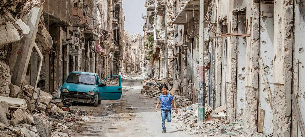 A child runs through the ruins of Benghazi, Libya.